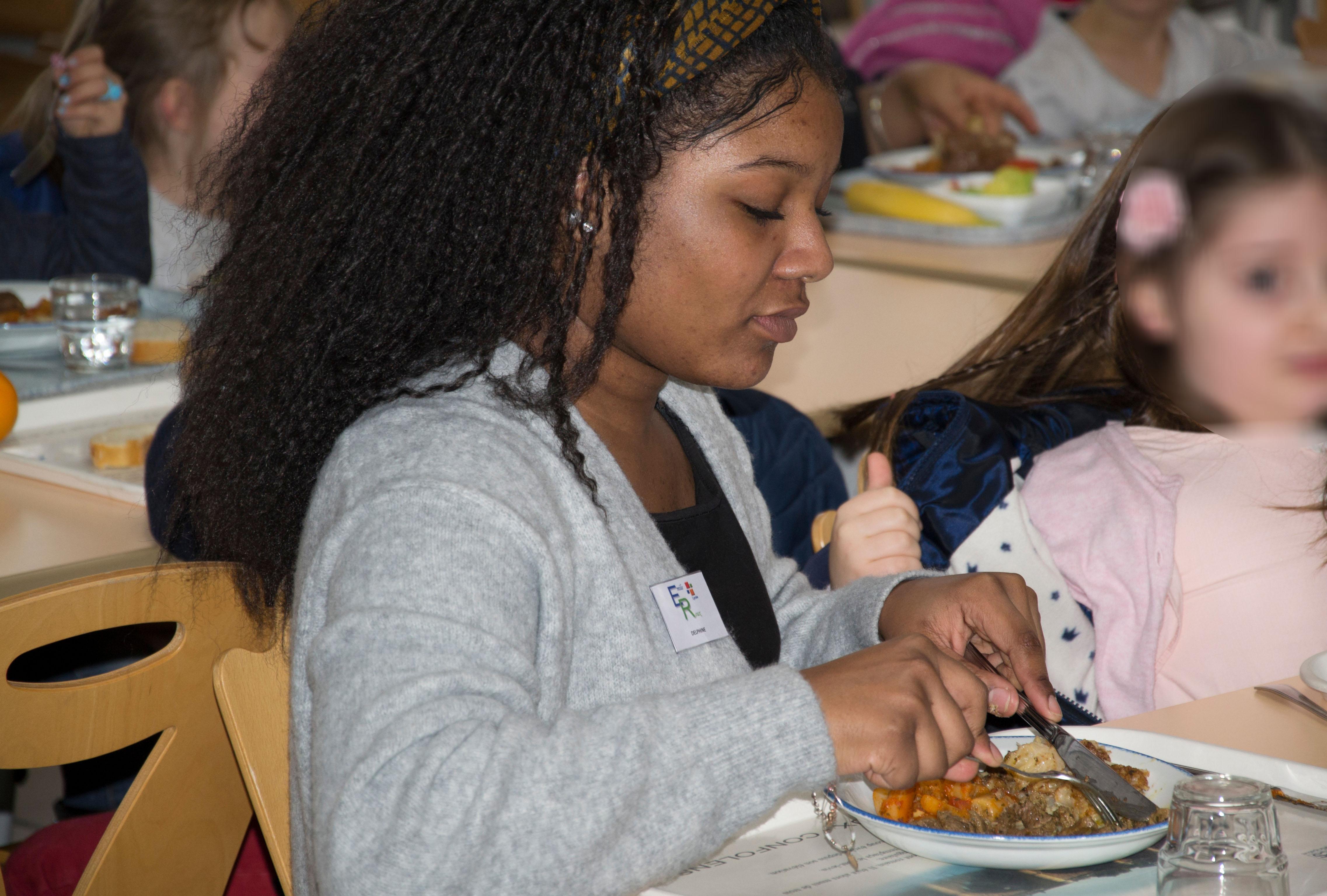 Une élève d'ASSP aidant une enfant à couper sa viande.